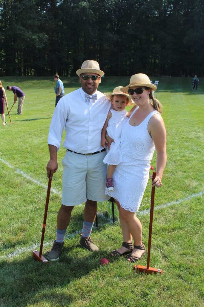 family smiles together while holding baby on croquet yard