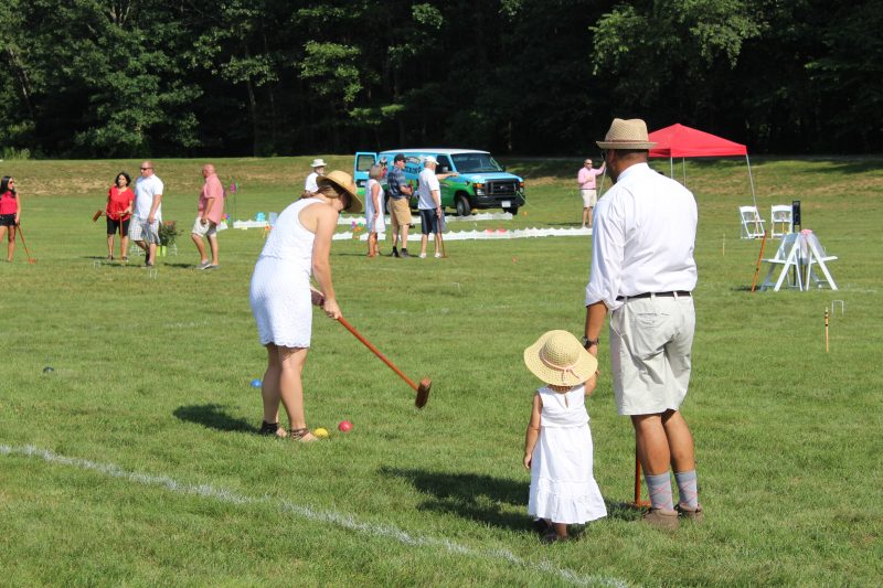 Family with young daughter playing croquet at Croquet on the Green