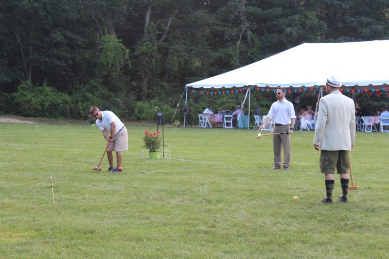 Croquet on the Green players watching man hit ball
