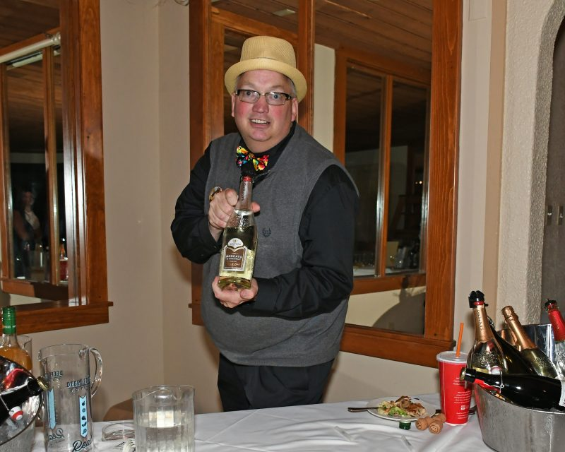 Keith Barnett presenting a bottle of Moscato
