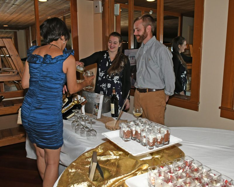 Vendor pouring a glass of wine for a woman