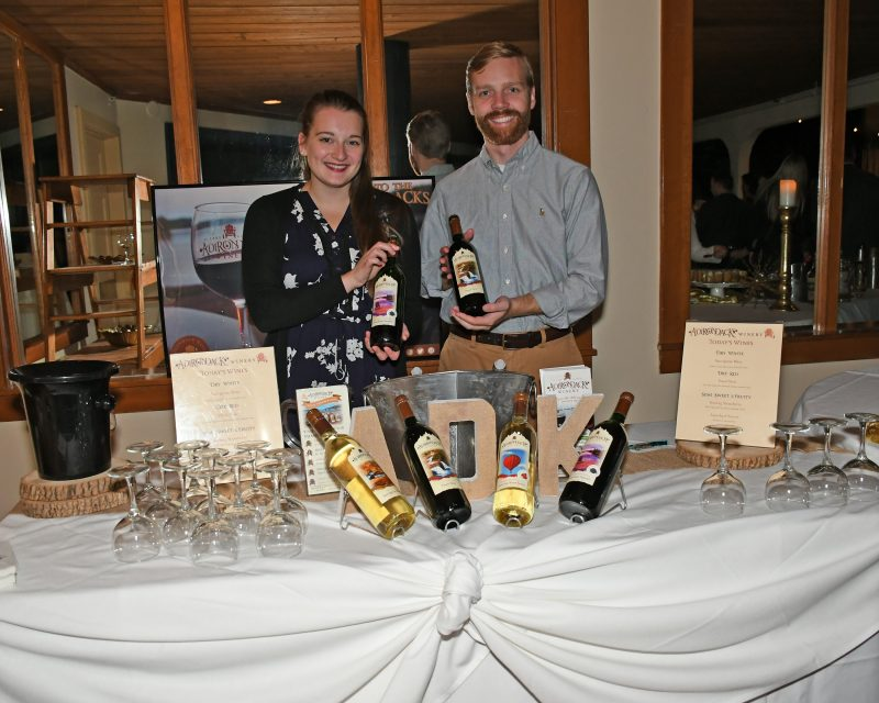 Stephanie Willis, Ethan Collins presenting bottles of Adirondack Winery Wine at the Vin Le Soir event