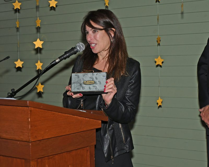 Artist Debbie Brooks presenting a Power of Potential clutch for AIM Services
