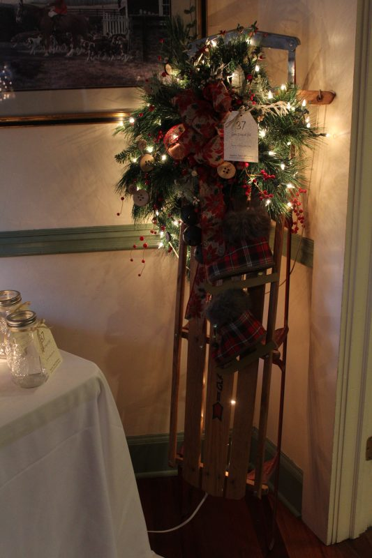 Raffle item wreath decorated on an old fashion sled at Vin Le Soir