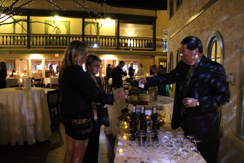 Brian Gwynn of Specialty Wines & More pouring a glass of wine for a woman at the Vin Le Soir event