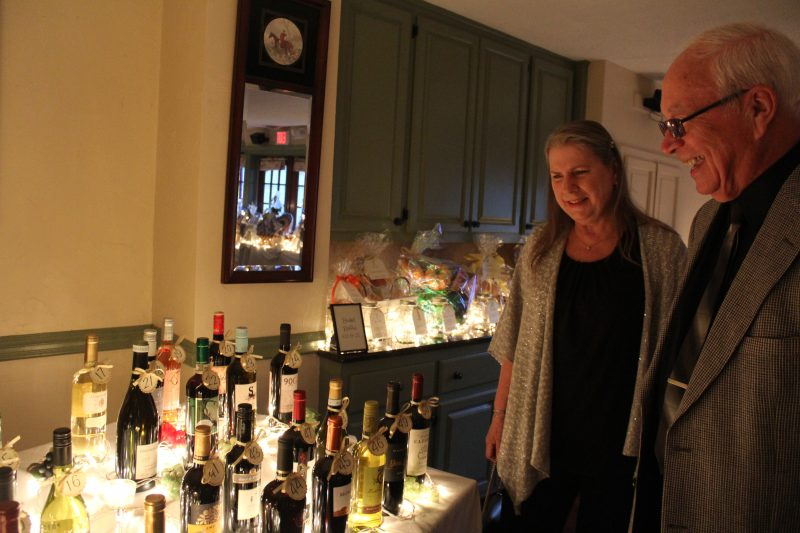 Man and woman smiling and looking at bottles of wine in a wine pull at Vin Le Soir event