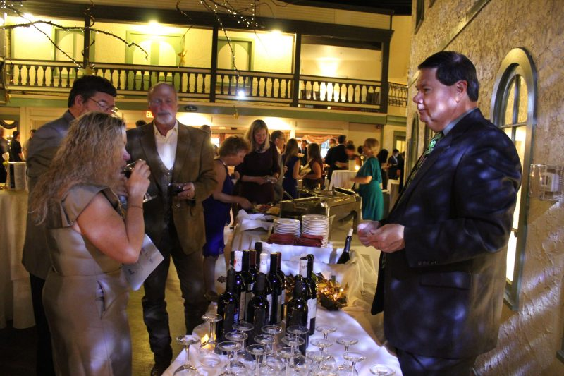 Woman tasting wine at the Specialty Wines & More vendor table at the Vin Le Soir event