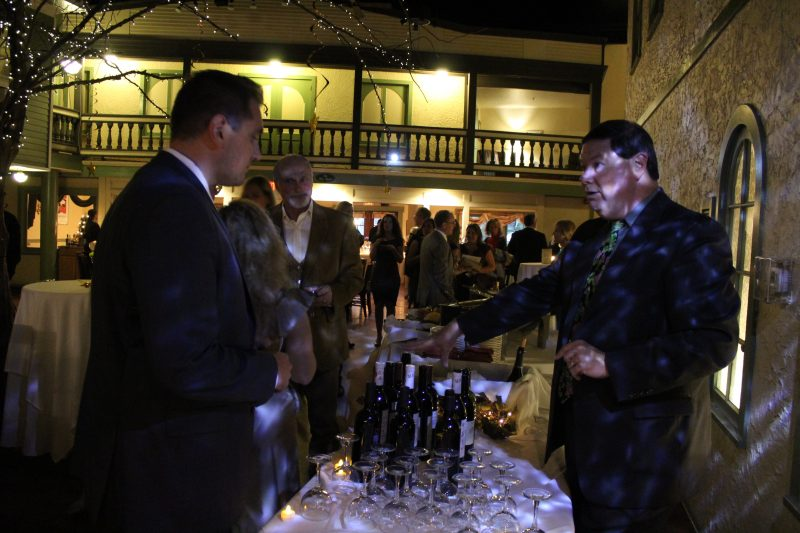 Brian Gwynn of Specialty Wines & More describing wine to a man at the Vin Le Soir event