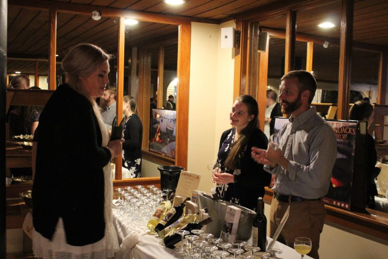 Staff from Adirondack Winery describing wine to a woman at the Vin Le Soir event