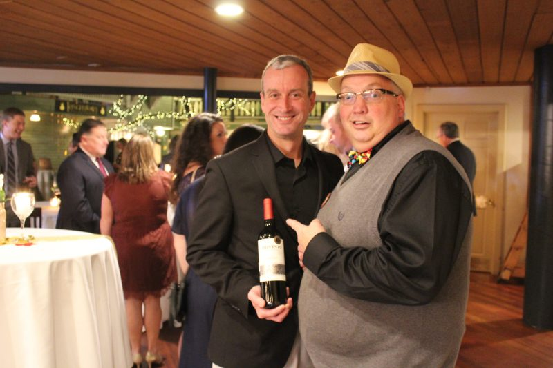 Keith Barnett pointing at Bill Blake holding a bottle of wine at the Vin Le Soir event