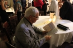 Man sitting at table with a glass of wine looking through the program of events for Vin Le Soir