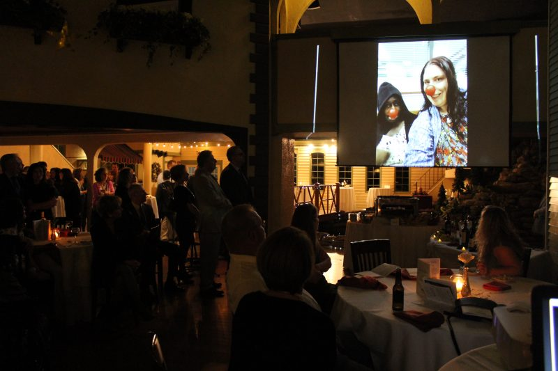 Attendees of Vin Le Soir watching a video