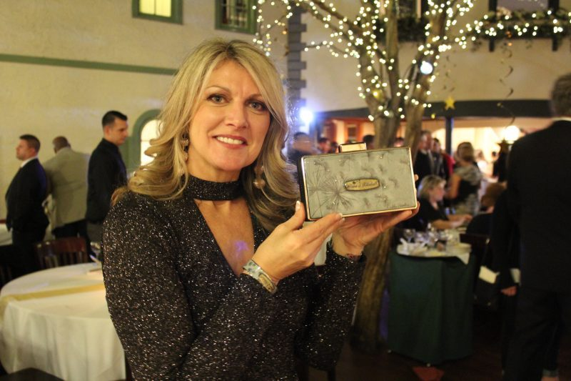 "Lynn Corbitt presenting a clutch engraved with ""power of potential"" designed by Debbie Brooks"