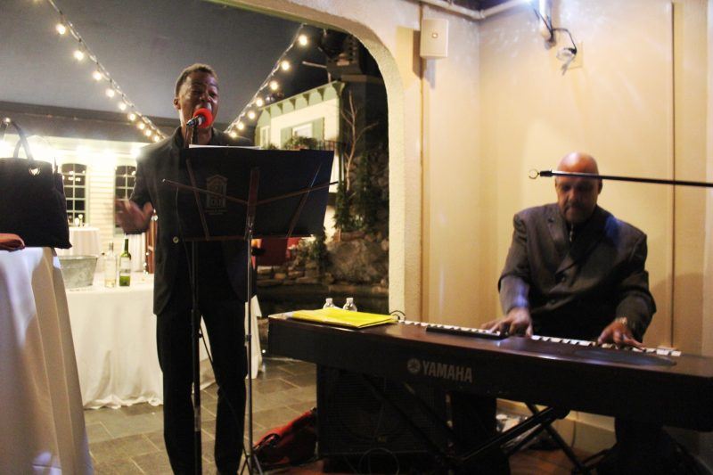 Azzaam Hameed playing keyboard with singer at Vin Le Soir event