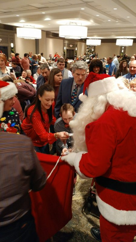 Group of people surrounding Santa as he hands out gifts from a bag at the Holiday Tea