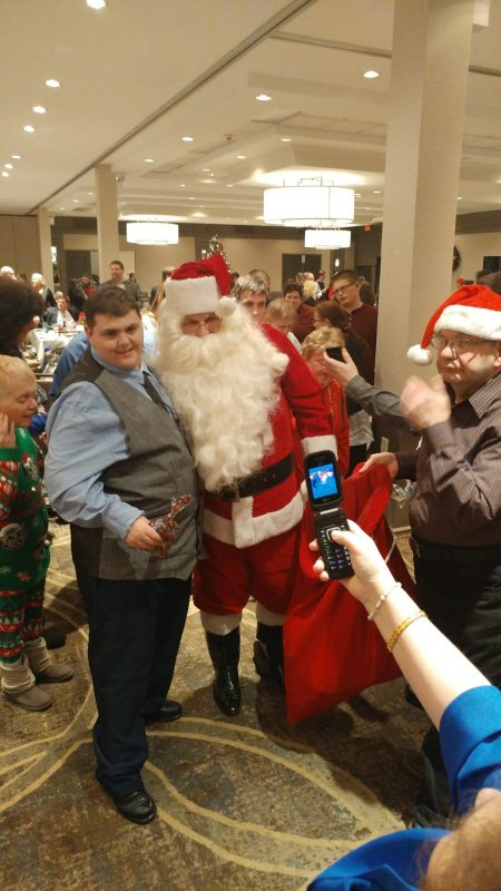 Man posing with Santa for a picture at the Holiday Tea event