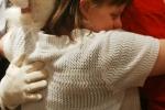 Woman hugging Santa at the Holiday Tea event