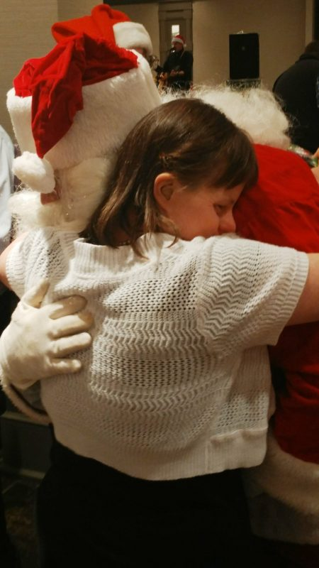 Woman hugging Santa at the Holiday Tea event