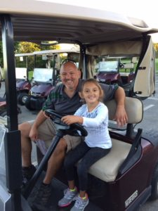 Bob and daughter Julianna on a golf cart