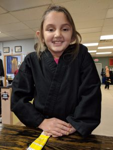Julianna in martial arts wear with a yellow belt