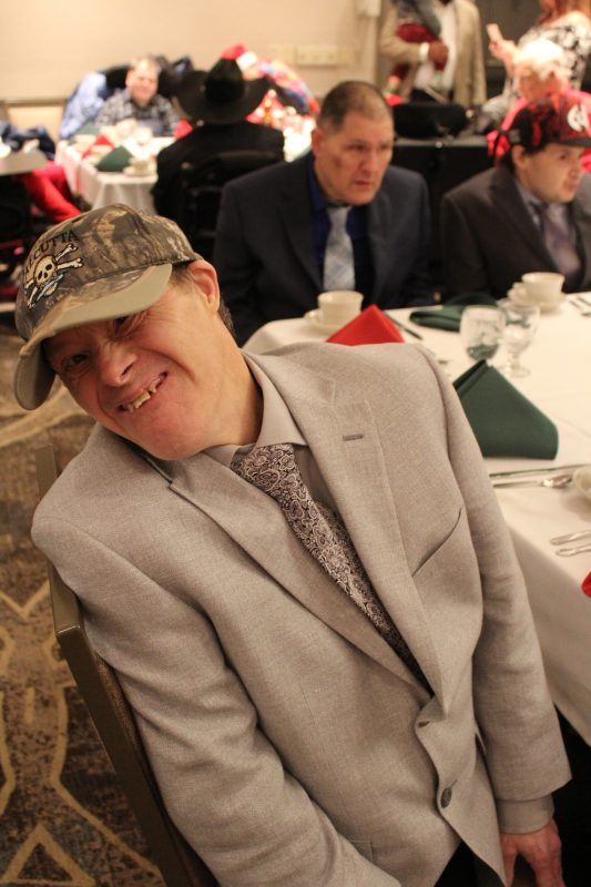 Man smiling at table at the Holiday Tea event