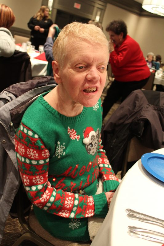 Woman smiling in Christmas sweater at the Holiday Tea event