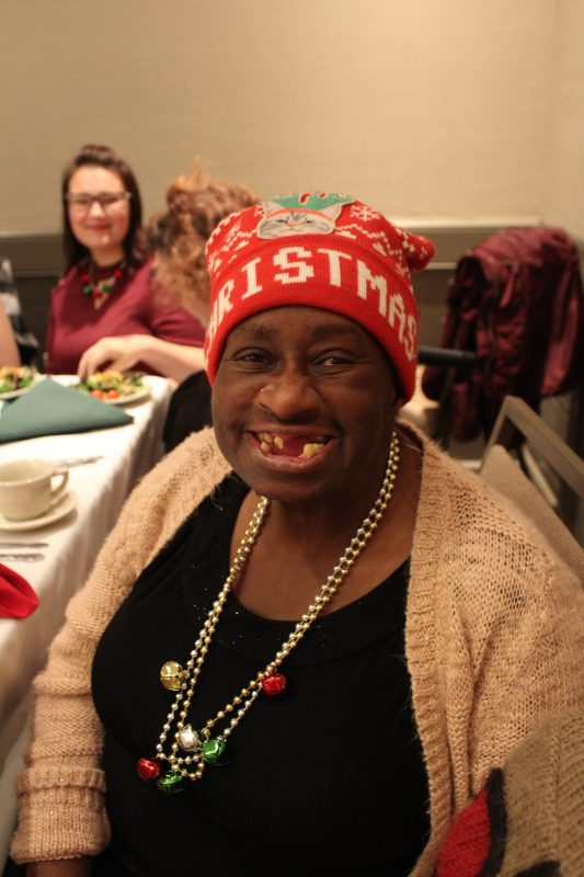 Woman smiling with Christmas hat on at the Holiday Tea event