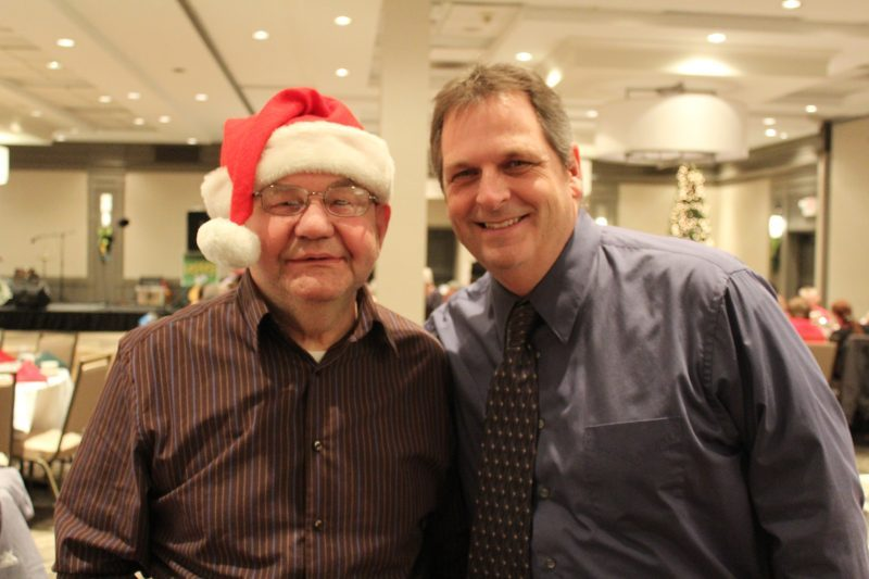 Man in Santa hat smiling with another man at the Holiday Tea event