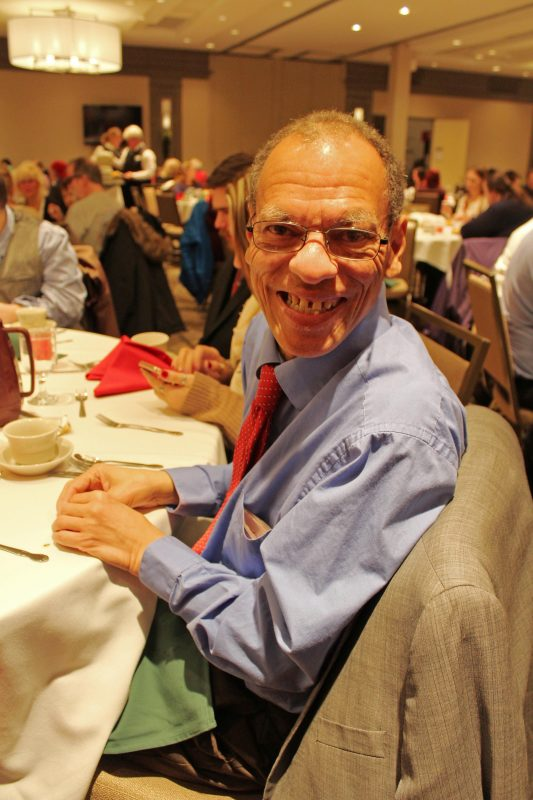 Man sitting at table smiling at the Holiday Tea party