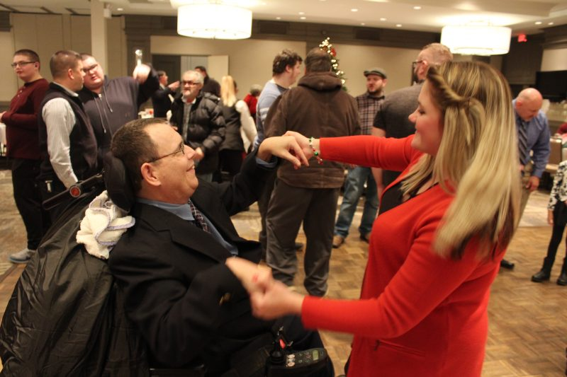 Man in wheelchair dancing with woman on at the Holiday Tea party
