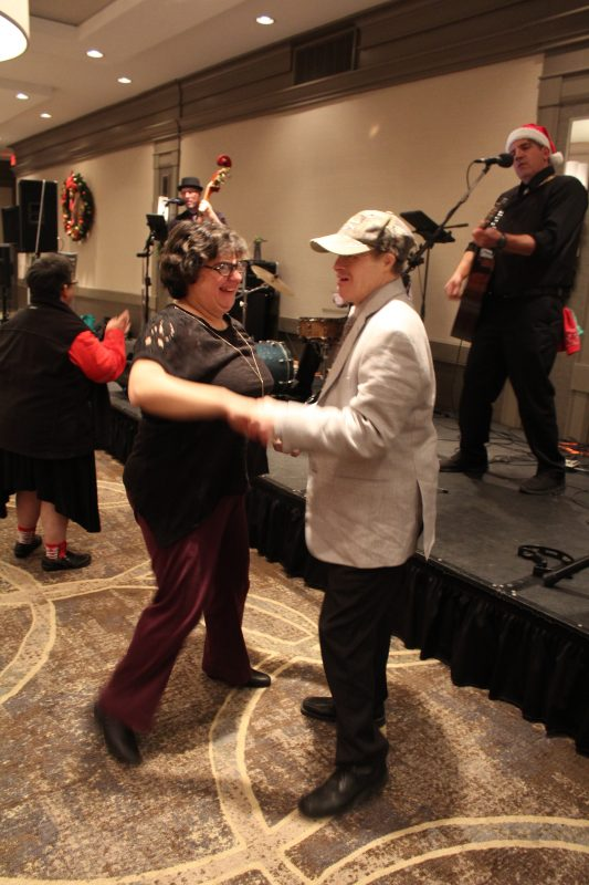 Two people dancing in front of the band at the Holiday Tea Party