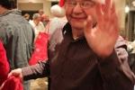 Man with Santa hat waving and smiling at the Holiday Tea party