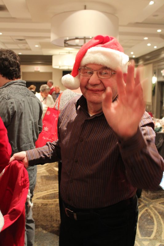 Man with Santa hat waving and smiling at the Holiday Tea party