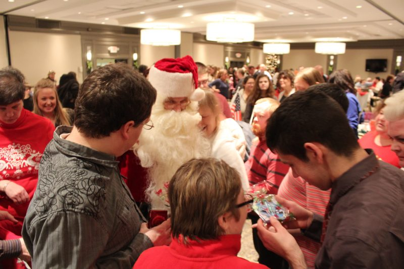 Group of people around Santa at Holiday Tea party