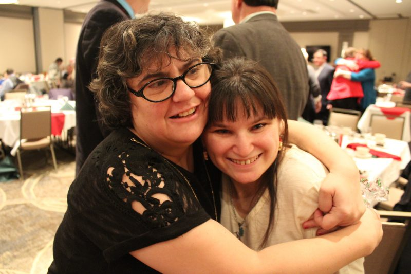 Two woman hugging and smiling at the Holiday Tea event