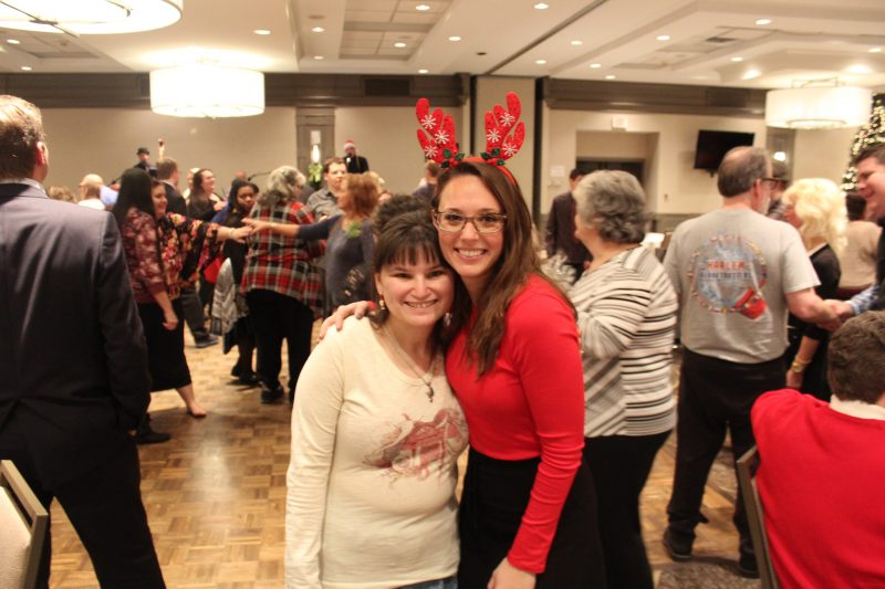 Two woman smiling on the dance floor at the Holiday Tea party
