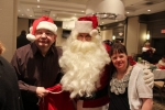 Two people smiling with Santa at the Holiday Tea event