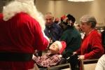 Man in wheelchair smiling up at Santa at the Holiday Tea party