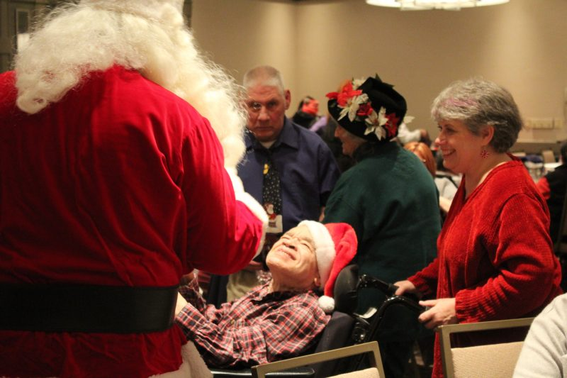 Man in wheelchair smiling up at Santa at the Holiday Tea party