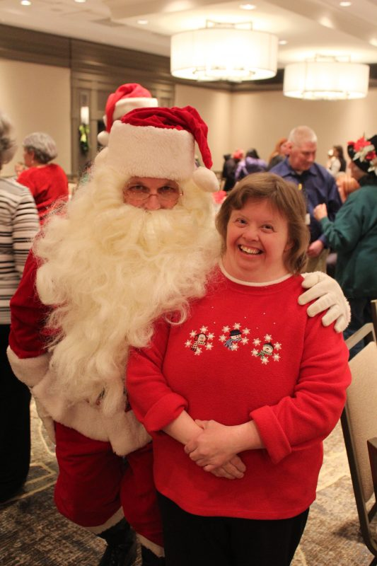 Woman smiling with Santa at the Holiday Tea party