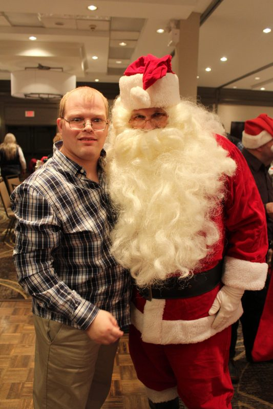 Man smiling with Santa at the Holiday Tea party
