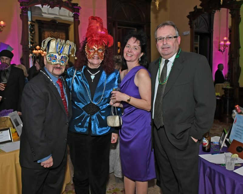 Group of four people, two with masks on, at Mardi Gras for AIM Services