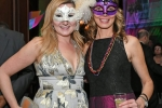 Two woman in dresses with matching mardi gras masks at Mardi Gras for AIM Services