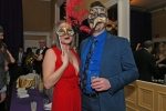 Two people, one dressed in all red and the other in all blue with matching masks on at Mardi Gras for AIM Services