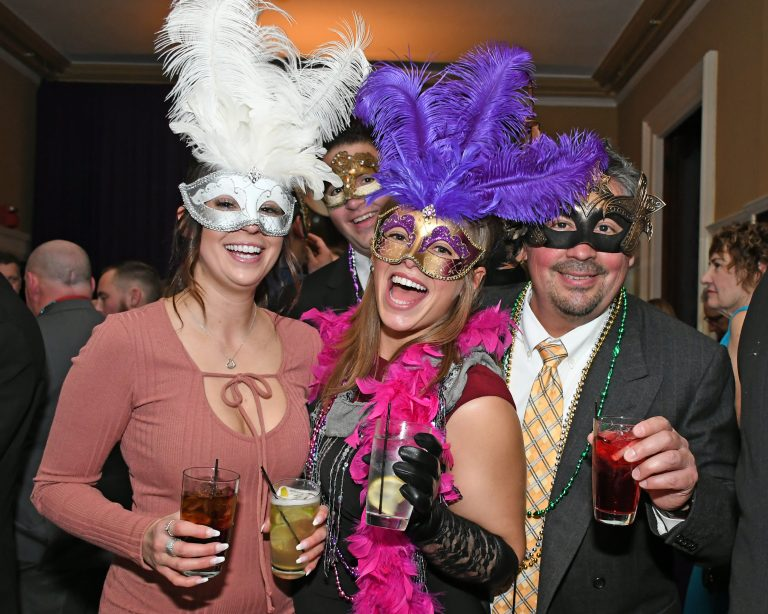 group of people in Mardi gras attire at event for AIM Services