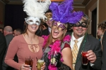Group of four people in mardi gras masks with feathers at Mardi Gras for AIM Services