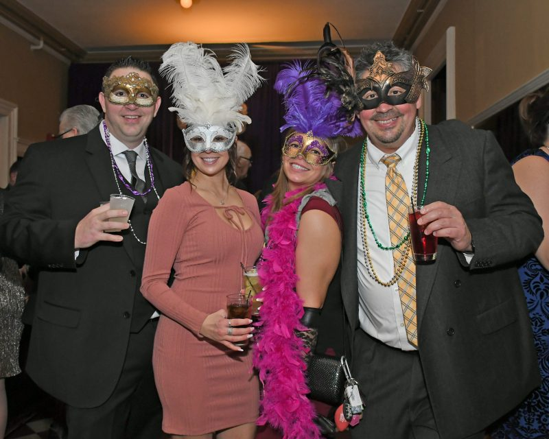 Four people smiling with feather masks on at Mardi Gras for AIM Services