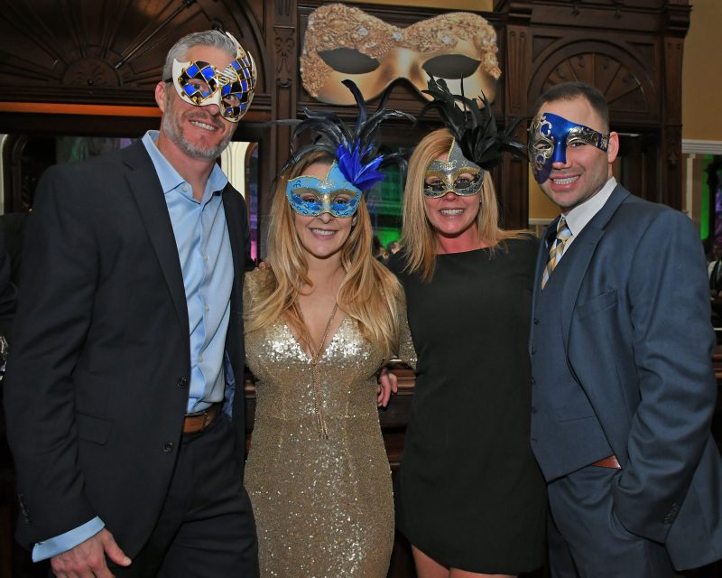 Group of four people with mardi gras masks on smiling at Mardi Gras for AIM Services