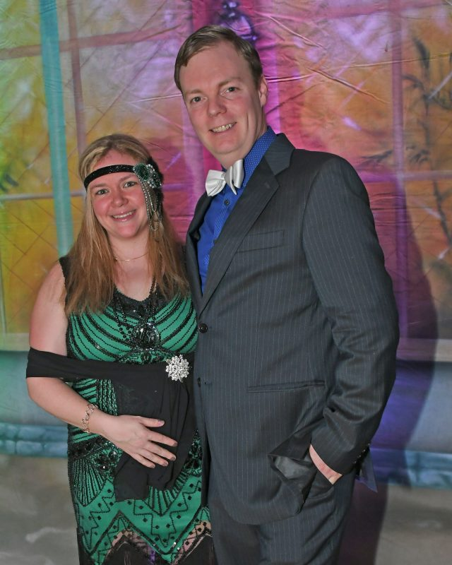 Woman dressed as a flapper with a man with a white bowtie smiling at Mardi Gras for AIM Services
