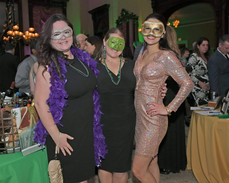 Three women in masks smiling at Mardi Gras for AIM Services